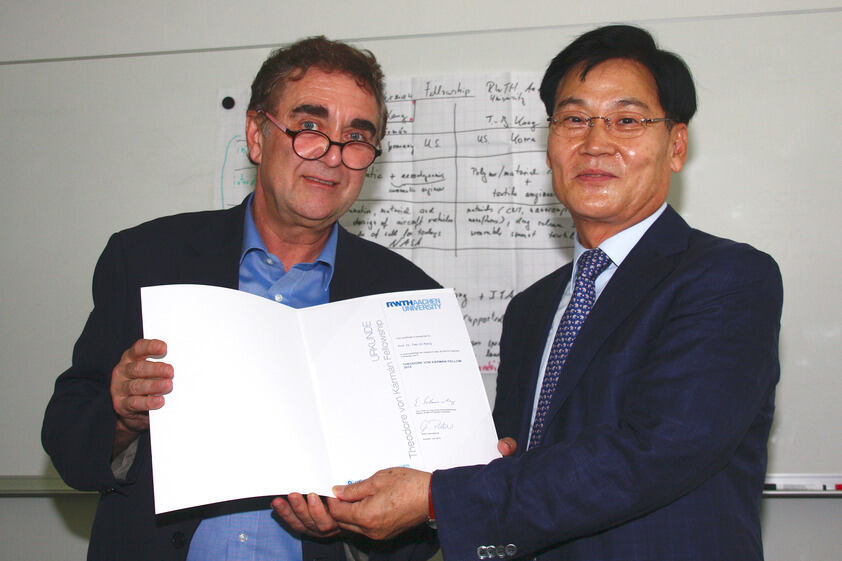 Rector's Delegate Prof. Manfred Martin gives Prof. Tae-Jin Kang the Kármán Fellowship certificate.