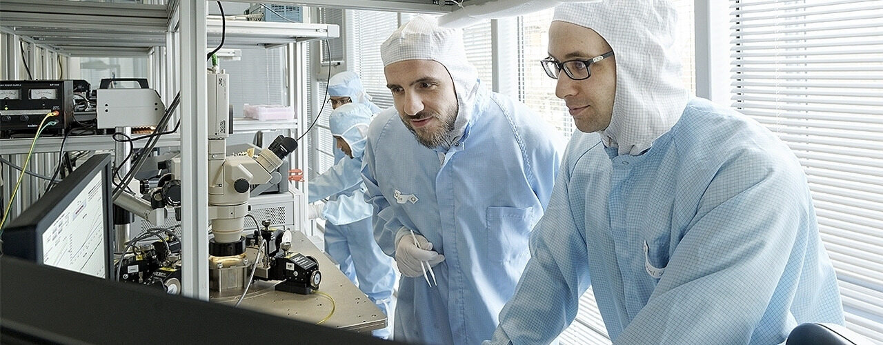 Researchers wearing protective suits in a cleanroom